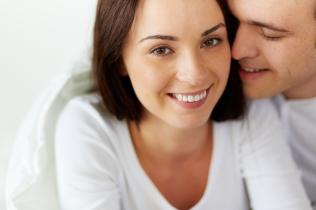 Portrait of smiling female looking at camera with her husband near by